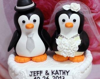 A penguin couple wedding cake topper. / white roses