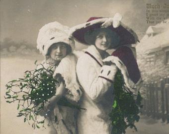 Hand colored  photo postcard of pretty girls in a winter scene. RPC, RPPC