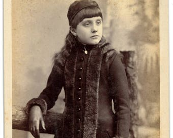 Beautiful cabinet card  a young girl wearing a hat, fur trimmed coat, leather gloves and a fur muff.
