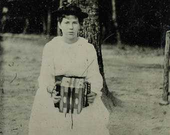 Tintype of a woman holding a concertina / accordion.
