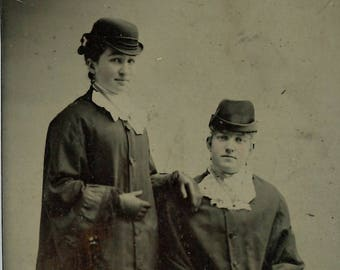 Tintype of two stylish women wearing Victorian coats and hats