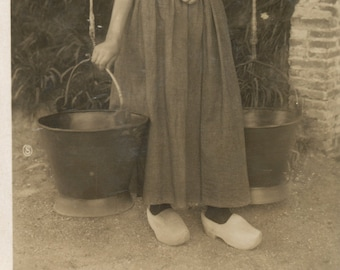 Real photo postcard of Dutch woman wearing wooden clogs and carrying milk buckets. RPC, RPPC