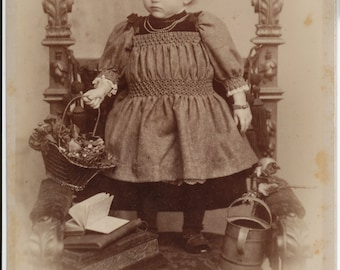 Cabinet card of child holding basket of flowers