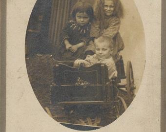 Three motley children in cart.