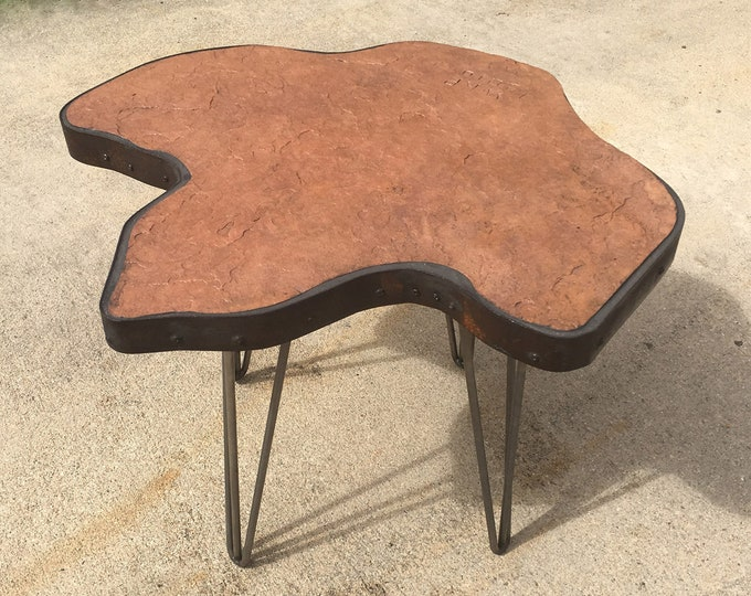 """Track #2: A natural stone topped table in the shape of a dinosaur track.  25""""x24""""x18"""" tall"""
