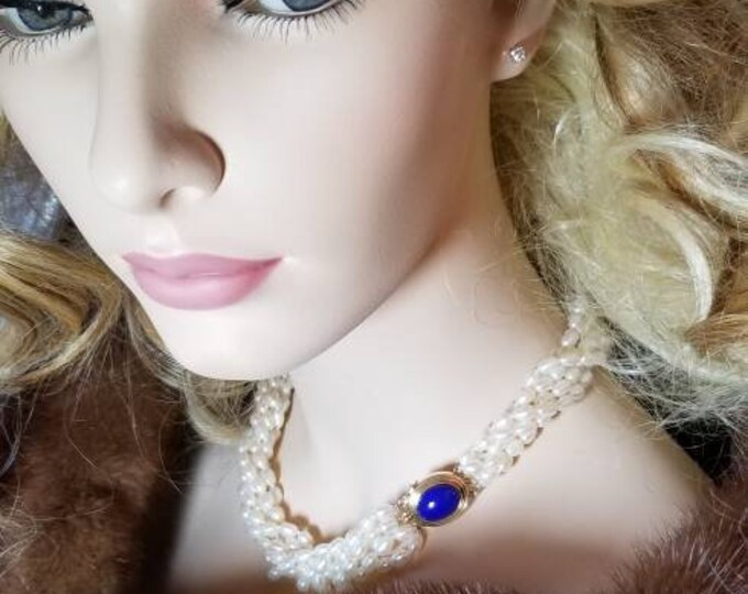 Cultured Freshwater Multi Strand Pearl Necklace. Attached to the Necklace is a 14K Yellow Gold Clasp Set with a Lapis Lazuli Gemstone.