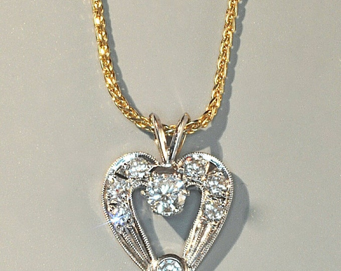 Hallmarked 14K White Gold Diamond Heart Shaped Pendant on a 14K Yellow Gold Wheat Chain. Approximate Total Diamond Weight is 0.97 cts.