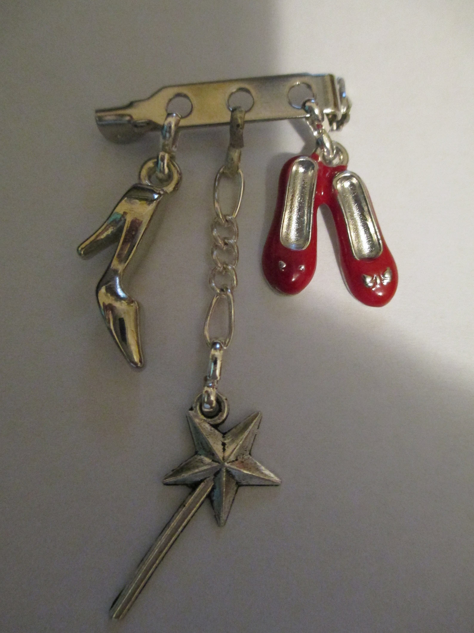 a brooch for fans of dorothy in wizard of oz, cinderella, ballet dancing, fairies,. red enamelled shoes, fairie/angle wand, sing