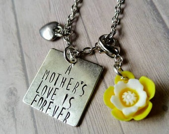 A mother's love is forever stamped necklace with a heart and flower charm