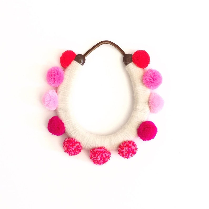 lucky yarn wrapped horseshoe with pink pom poms image 0