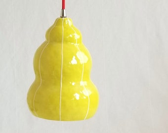 Yellow ceramic pendant light fixture. Red plug in cord