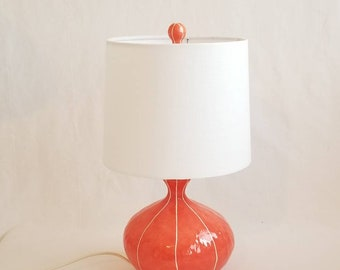 Coral red table lamp. Bedroom decor, accent lighting