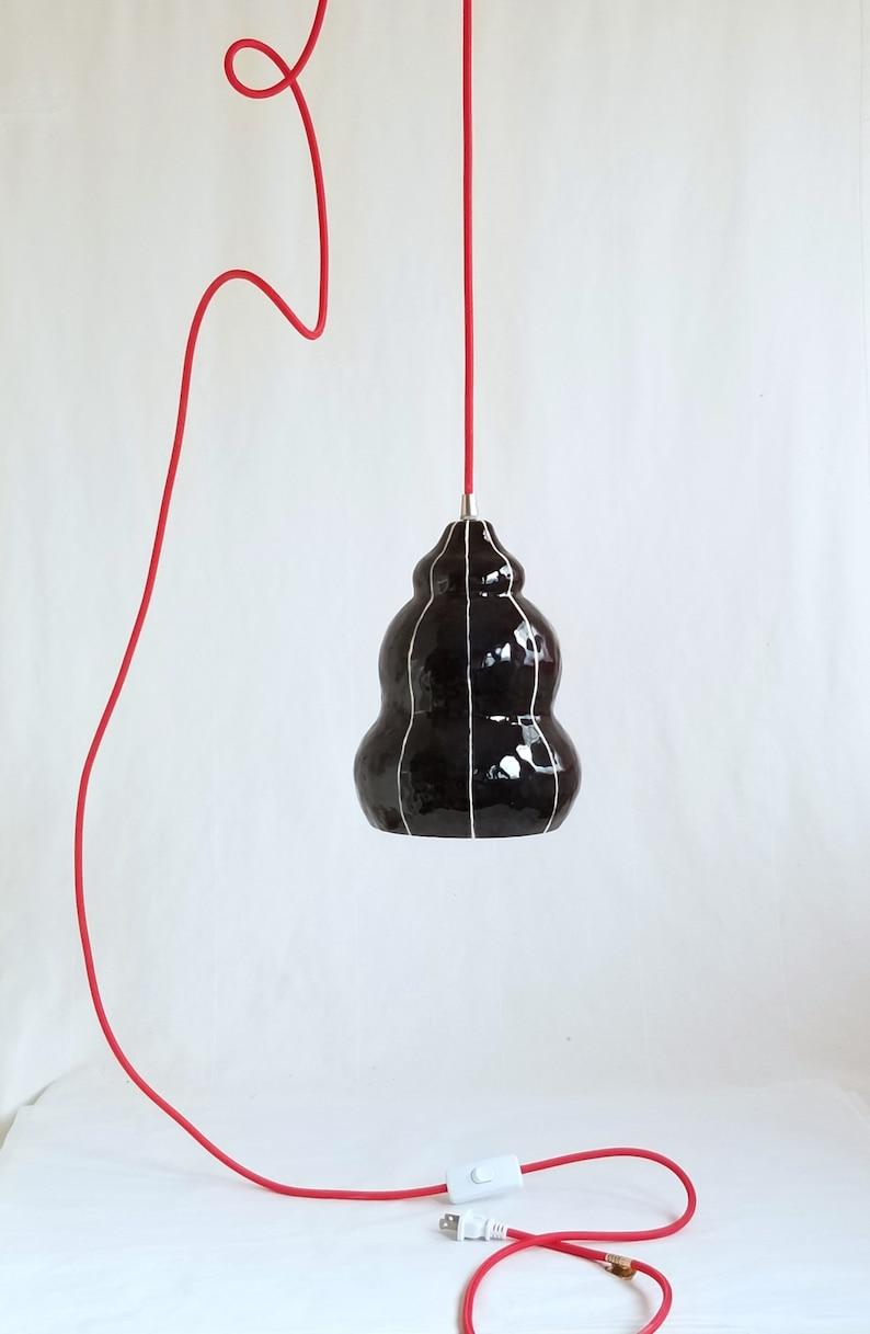 Black ceramic pendant light fixture. Red plug in cord Black