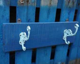 Distressed paint, 2 hook coat rack. Solid royal blue painted board with 2 iron hooks.