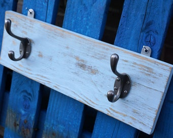 Distressed paint, 2 hook coat rack. Light blue/grey painted board with 2 heavy iron hooks.