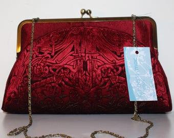 A deep crimson red kisslock clutch bag in an embossed iridescent velvet celtic design