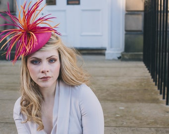 Pink felt percher hat with orange/magenta feathers perfect for weddings or races/derby event