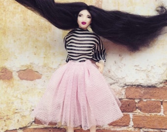 Miniature doll in pink with very spoiled lips