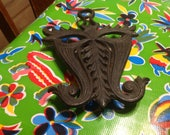 Vintage Doodlers Dream heavy black cast iron Mardi Gras mask trivet