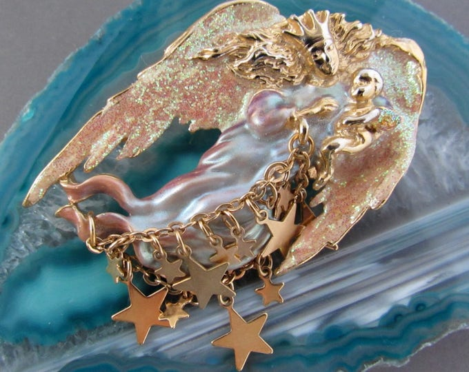 Vintage Kirks Folly large glittering winged guardian Angel who carries a baby opalescent enameled  brooch with celestial star charms