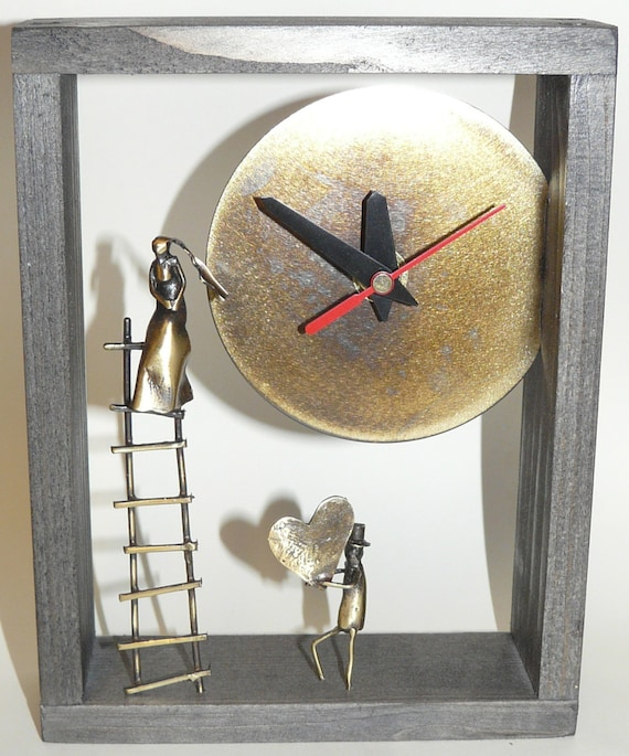 Lover's clock in ebony color wooden frame.