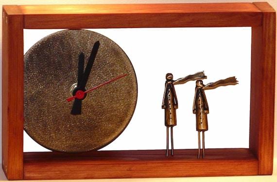 Desk bronze clock with light brown wooden frame.