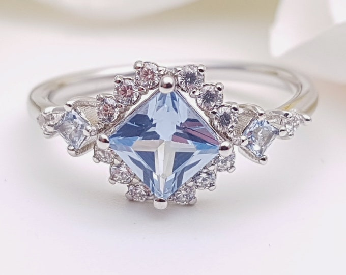 Aquamarine Princess cut man made diamond halo solitaire engagement ring available in Rose, yellow or white gold