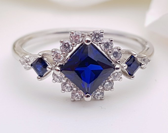 Blue Sapphire Princess cut man made diamond halo solitaire engagement ring available in Rose, yellow or white gold and platinum