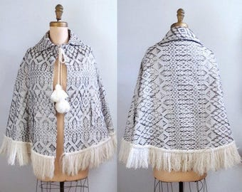 Whimsy tales   1960s white cape with silver lurex pattern   60s fringed poncho with folkloric design