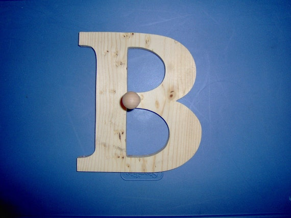 8 Inch decorative wooden letter with peg. Handmade in the USA. Made out of pine wood.