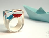 Ship ahoy – maritime boat ring with hand-made folded mini boats made of red and blue paper on a white ring made of resin