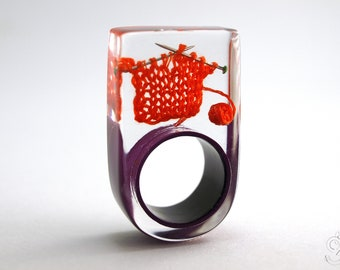 Knitting – extraordinary knitting ring with orange-red knitted wool and knitting needles on a purple ring made of resin