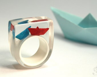 """Paper boat ring """"Ship ahoy"""" with hand-made folded mini boats made of red and blue paper on a white ring made of resin"""