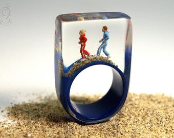 Early morning exercise – sportive jogger-figures ring with mini-figures and sand on a dark blue ring made of resin for the daily training