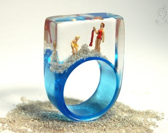 Summer breeze – summerlike beach figure ring with mini figures and sand on a light blue ring made of resin for the holiday feeling