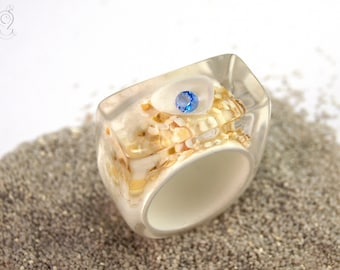 Flotsam – mysterious ring with a blue zirconia gemstone in a shell on a white ring with sand made of resin for all treasure hunters