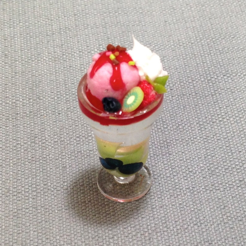 Puppenhaus Erdbeere und Kiwi Törtchen auf einem Teller mit einem Löffel