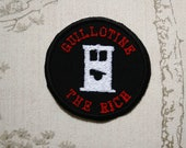 Whimsy merit embroidered iron on patch: Guillotine the rich.