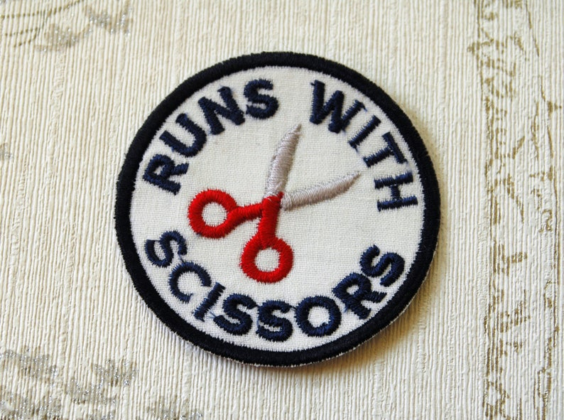 Crafting merit embroidered iron on patch: Runs with scissors. image 0