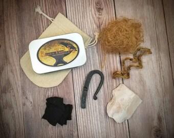 Fire kit including: hand forged striker, stone flake, char cloth, tinder, storage tin, & canvas sack