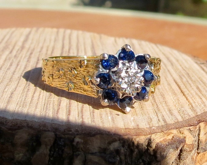 Gold sapphire ring. Vintage 18K yellow gold blue sapphire and diamond daisy ring, with forget-me-not flower accents, from 1977