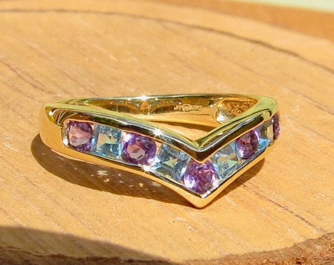 A 9k yellow gold blue topaz and amethyst wishbone ring