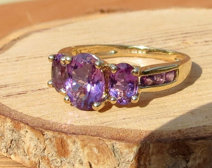 A 9k yellow gold amethyst trilogy ring