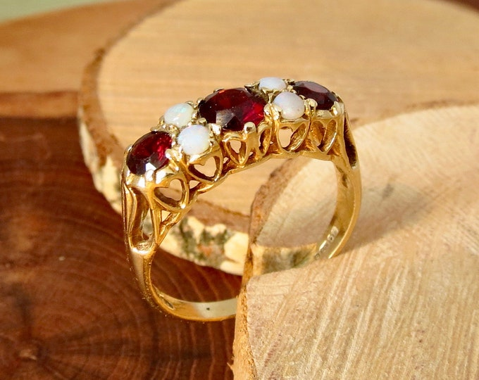 A vintage 9K yellow gold ring, heart gallery with a graduated red garnets and opal cabochon accents.