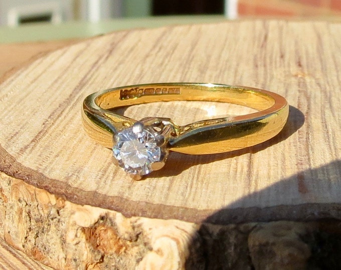 An 18K yellow gold 1/4 Carat diamond solitaire ring.