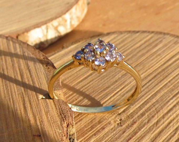 Gold topaz ring. A 9k yellow gold ring has 9 round cut lavender topaz set in a cluster setting