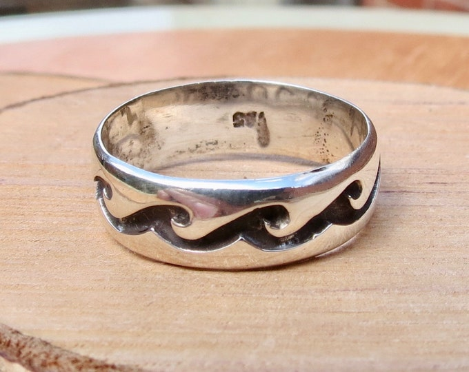 A silver ring with decorative wave design.