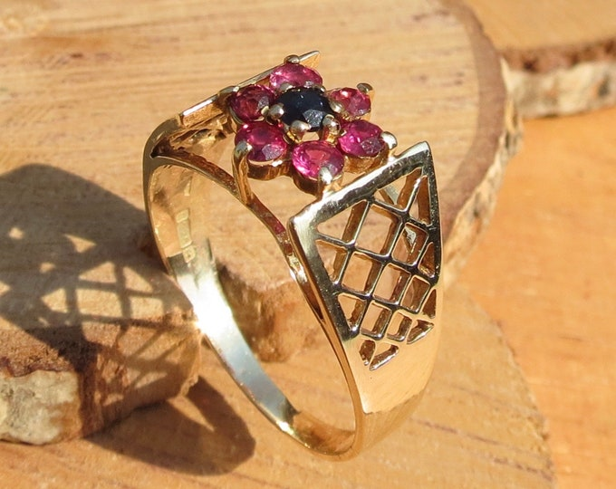 Gold ruby sapphire ring. 9k yellow gold ring has six round cut rubies and a central blue sapphire, mounted in a daisy arrangement.