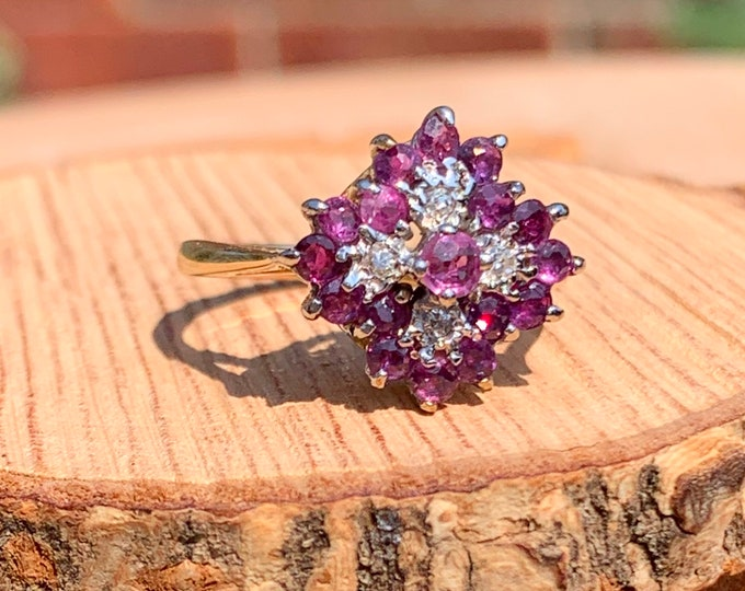 Gold ruby ring. A 9K yellow gold ring, with round cut reddish purple rubies and diamond accents, vintage 1980s