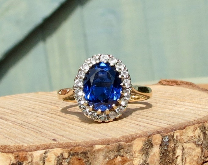 A 9k yellow gold 2 carat blue spinel and white stone ring.